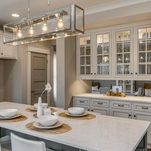 ナッシュビルの中サイズのトランジショナルスタイルのおしゃれなキッチン (アンダーカウンターシンク、フラットパネル扉のキャビネット、白いキャビネット、クオーツストーンカウンター、グレーのキッチンパネル、サブウェイタイルのキッチンパネル、シルバーの調理設備、無垢フローリング) の写真