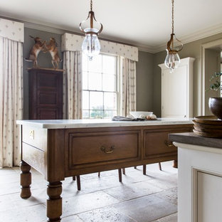This is an example of a large classic galley kitchen/diner in London with a single-bowl sink, raised-panel cabinets, white cabinets, marble worktops, integrated appliances, limestone flooring, an island and beige floors.