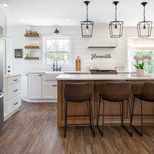 Inspiration för ett mellanstort lantligt vit vitt kök, med en rustik diskho, skåp i shakerstil, vita skåp, bänkskiva i kvarts, vitt stänkskydd, stänkskydd i trä, rostfria vitvaror, vinylgolv, en köksö och brunt golv