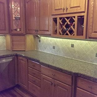 Küche mit hellen Holzschränken, Granit-Arbeitsplatte und Küchengeräten aus Edelstahl in Sonstige