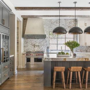 Country Küche in L-Form mit Schrankfronten im Shaker-Stil, grauen Schränken, Rückwand aus Backstein, Küchengeräten aus Edelstahl, braunem Holzboden, Kücheninsel, braunem Boden und beiger Arbeitsplatte in Dallas