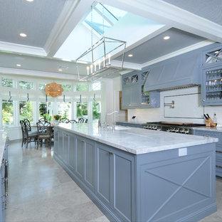 Klassisk inredning av ett vit vitt u-kök, med en undermonterad diskho, luckor med profilerade fronter, blå skåp, vitt stänkskydd, stänkskydd i tunnelbanekakel, rostfria vitvaror, en köksö och grått golv