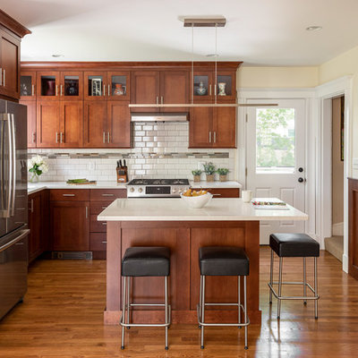 Kitchen - mid-sized craftsman l-shaped medium tone wood floor and brown floor kitchen idea in Boston with an undermount sink, shaker cabinets, medium tone wood cabinets, quartz countertops, white backsplash, subway tile backsplash, stainless steel appliances, an island and white countertops
