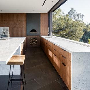 Пример оригинального дизайна: угловая кухня в стиле модернизм с врезной раковиной, плоскими фасадами, фасадами цвета дерева среднего тона, фартуком с окном, техникой из нержавеющей стали, островом, серым полом и белой столешницей