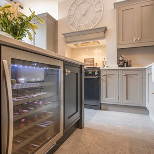Photo of a large classic l-shaped kitchen/diner in Other with a belfast sink, shaker cabinets, grey cabinets, granite worktops, stainless steel appliances, cement flooring, an island and grey floors.