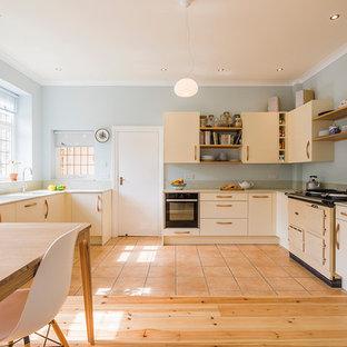 他の地域の中くらいのコンテンポラリースタイルのおしゃれなキッチン (一体型シンク、フラットパネル扉のキャビネット、白いキャビネット、ガラスカウンター、緑のキッチンパネル、ガラス板のキッチンパネル、パネルと同色の調理設備、セラミックタイルの床、アイランドなし、オレンジの床) の写真