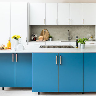 Inspiration for a large contemporary kitchen in London with an integrated sink, flat-panel cabinets, turquoise cabinets, concrete benchtops, grey splashback, slate splashback, stainless steel appliances, light hardwood floors, with island and grey floor.