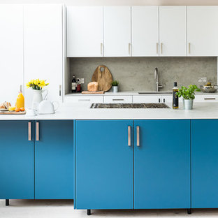 Design ideas for a large contemporary kitchen in London with an integrated sink, flat-panel cabinets, turquoise cabinets, concrete benchtops, grey splashback, slate splashback, stainless steel appliances, light hardwood floors, with island and grey floor.