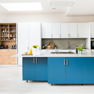 Photo of a large contemporary galley open plan kitchen in London with an integrated sink, flat-panel cabinets, turquoise cabinets, concrete benchtops, grey splashback, slate splashback, stainless steel appliances, light hardwood floors, with island, grey floor and grey benchtop.