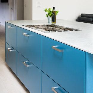 Exempel på ett stort modernt kök, med en integrerad diskho, släta luckor, turkosa skåp, bänkskiva i betong, grått stänkskydd, stänkskydd i skiffer, rostfria vitvaror, ljust trägolv, en köksö och grått golv