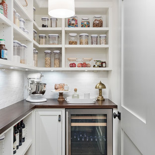 This is an example of a transitional l-shaped kitchen pantry in Detroit with open cabinets, white cabinets, wood benchtops, white splashback, stainless steel appliances, dark hardwood floors, brown floor and brown benchtop.