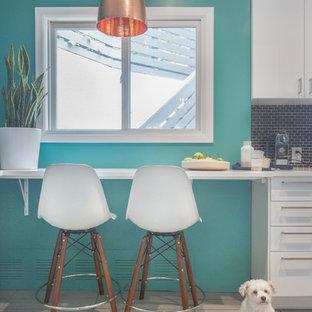 サンフランシスコの中くらいのミッドセンチュリースタイルのおしゃれなキッチン (エプロンフロントシンク、フラットパネル扉のキャビネット、白いキャビネット、青いキッチンパネル、セラミックタイルのキッチンパネル、シルバーの調理設備、セラミックタイルの床、アイランドなし、クオーツストーンカウンター、グレーの床) の写真