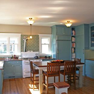 Immagine di una cucina chic di medie dimensioni con lavello a vasca singola, ante di vetro, ante blu, elettrodomestici bianchi, pavimento in legno massello medio, paraspruzzi blu, paraspruzzi con piastrelle diamantate e top in rame