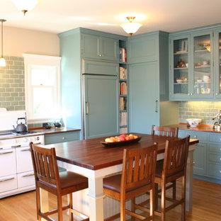 Exempel på ett mellanstort klassiskt kök, med luckor med glaspanel, bänkskiva i akrylsten, blå skåp, blått stänkskydd, stänkskydd i tunnelbanekakel, vita vitvaror, en enkel diskho, mellanmörkt trägolv och en köksö