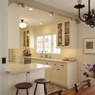 サンフランシスコの小さい地中海スタイルのおしゃれなキッチン (アンダーカウンターシンク、シェーカースタイル扉のキャビネット、白いキャビネット、クオーツストーンカウンター、白いキッチンパネル、サブウェイタイルのキッチンパネル、シルバーの調理設備、セラミックタイルの床、アイランドなし) の写真