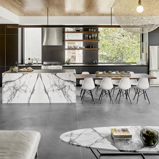 This is an example of a mid-sized midcentury galley open plan kitchen in San Francisco with an undermount sink, black cabinets, black splashback, stone slab splashback, stainless steel appliances, concrete floors, with island and flat-panel cabinets.