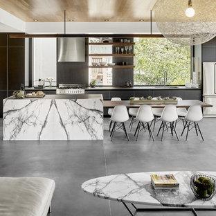 Idéer för ett mellanstort 60 tals kök, med en undermonterad diskho, svarta skåp, svart stänkskydd, stänkskydd i sten, rostfria vitvaror, betonggolv, en köksö och släta luckor