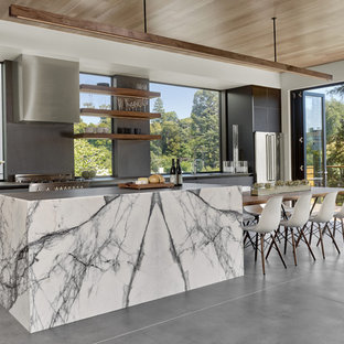 This is an example of a mid-sized modern galley open plan kitchen in San Francisco with an undermount sink, glass-front cabinets, black cabinets, black splashback, stone slab splashback, stainless steel appliances, concrete floors and with island.