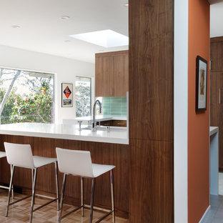 Mittelgroße Retro Küche in L-Form mit Unterbauwaschbecken, flächenbündigen Schrankfronten, dunklen Holzschränken, Mineralwerkstoff-Arbeitsplatte, Küchenrückwand in Grün, Rückwand aus Keramikfliesen, Küchengeräten aus Edelstahl, Porzellan-Bodenfliesen und Halbinsel in San Francisco