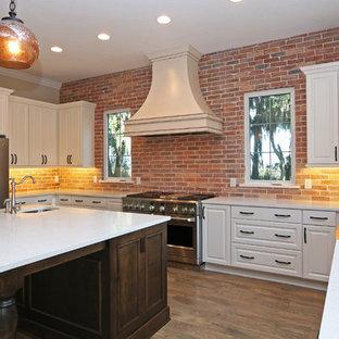 オーランドの中くらいのカントリー風おしゃれなキッチン (エプロンフロントシンク、レイズドパネル扉のキャビネット、白いキャビネット、人工大理石カウンター、赤いキッチンパネル、レンガのキッチンパネル、シルバーの調理設備、濃色無垢フローリング) の写真