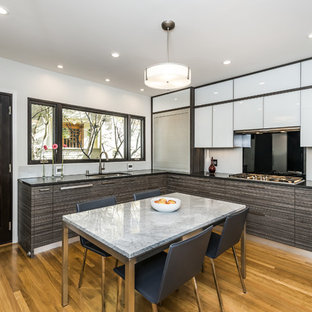 Mid-sized contemporary enclosed kitchen ideas - Example of a mid-sized trendy l-shaped medium tone wood floor and brown floor enclosed kitchen design in San Francisco with an undermount sink, flat-panel cabinets, brown cabinets, solid surface countertops, white backsplash, glass sheet backsplash, paneled appliances and black countertops