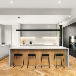 Contemporary u-shaped kitchen in Melbourne with a double-bowl sink, flat-panel cabinets, grey cabinets, white splashback, panelled appliances, medium hardwood floors, with island, brown floor and white benchtop.