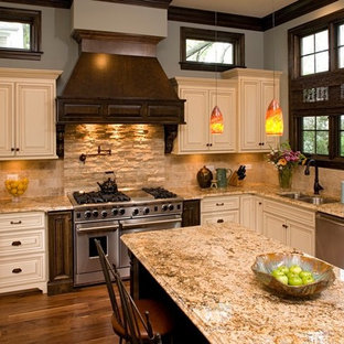 Mid-sized traditional enclosed kitchen photos - Example of a mid-sized classic u-shaped medium tone wood floor enclosed kitchen design in Chicago with a double-bowl sink, raised-panel cabinets, beige cabinets, beige backsplash, granite countertops, stainless steel appliances, an island and travertine backsplash