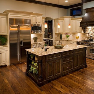 This is an example of a medium sized traditional u-shaped enclosed kitchen in Chicago with raised-panel cabinets, beige cabinets, beige splashback, stone tiled splashback, stainless steel appliances, granite worktops, an island, a double-bowl sink and dark hardwood flooring.