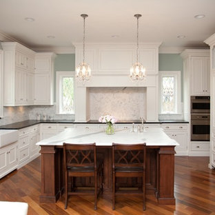 Traditional kitchen designs - Elegant kitchen photo in Chicago with recessed-panel cabinets, a farmhouse sink, white cabinets, white backsplash and stone tile backsplash