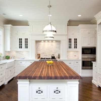 Enclosed kitchen - mid-sized traditional l-shaped dark wood floor enclosed kitchen idea in Chicago with recessed-panel cabinets, a farmhouse sink, wood countertops, white cabinets, white backsplash, stone tile backsplash, stainless steel appliances and an island