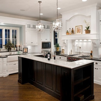 Inspiration for a mid-sized timeless l-shaped medium tone wood floor enclosed kitchen remodel in Chicago with marble countertops, stainless steel appliances, a farmhouse sink, recessed-panel cabinets, white backsplash, subway tile backsplash and an island
