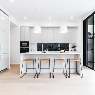 Design ideas for a mid-sized modern l-shaped kitchen in Sydney with flat-panel cabinets, grey cabinets, window splashback, black appliances, light hardwood floors, with island, beige floor and white benchtop.