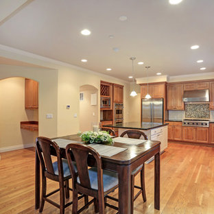 Mid-sized traditional l-shaped eat-in kitchen in DC Metro with an undermount sink, raised-panel cabinets, brown cabinets, granite benchtops, yellow splashback, ceramic splashback, stainless steel appliances, light hardwood floors, with island, brown floor and green benchtop.