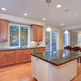 Inspiration for a mid-sized traditional l-shaped eat-in kitchen in DC Metro with an undermount sink, raised-panel cabinets, brown cabinets, granite benchtops, yellow splashback, ceramic splashback, stainless steel appliances, light hardwood floors, with island, brown floor and green benchtop.