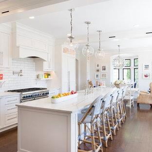 Foto de cocina comedor costera con armarios estilo shaker, puertas de armario blancas, salpicadero blanco, electrodomésticos de acero inoxidable, suelo de madera en tonos medios y una isla