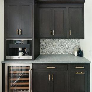 Foto di una piccola cucina tradizionale con ante a filo, ante nere, top in saponaria, paraspruzzi con piastrelle di cemento, parquet scuro e isola