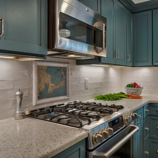 This is an example of a small modern l-shaped kitchen pantry in Boston with a belfast sink, shaker cabinets, blue cabinets, recycled glass countertops, white splashback, ceramic splashback, stainless steel appliances, ceramic flooring, an island and beige floors.