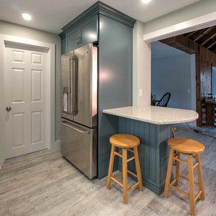 Modern inredning av ett litet kök, med en rustik diskho, skåp i shakerstil, blå skåp, bänkskiva i återvunnet glas, vitt stänkskydd, stänkskydd i keramik, rostfria vitvaror, klinkergolv i keramik, en köksö och beiget golv