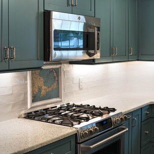 Small modern l-shaped kitchen pantry in Boston with a belfast sink, shaker cabinets, blue cabinets, recycled glass countertops, white splashback, ceramic splashback, stainless steel appliances, ceramic flooring, an island and beige floors.