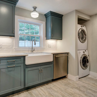 This is an example of a small modern l-shaped kitchen pantry in Boston with a farmhouse sink, shaker cabinets, blue cabinets, recycled glass benchtops, white splashback, ceramic splashback, stainless steel appliances, ceramic floors, with island and beige floor.