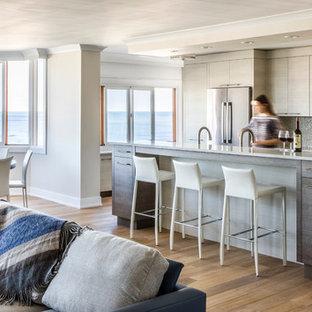 ニューヨークの中サイズのビーチスタイルのおしゃれなキッチン (フラットパネル扉のキャビネット、淡色木目調キャビネット、メタリックのキッチンパネル、モザイクタイルのキッチンパネル、シルバーの調理設備の、無垢フローリング、御影石カウンター) の写真