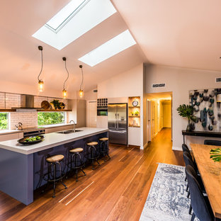 Large industrial galley eat-in kitchen in Sydney with an undermount sink, quartz benchtops, white splashback, stainless steel appliances, porcelain floors, with island, orange floor, flat-panel cabinets, beige cabinets and subway tile splashback.