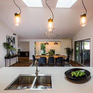 Inspiration for a large contemporary galley eat-in kitchen in Sydney with a triple-bowl sink, flat-panel cabinets, beige cabinets, quartz benchtops, white splashback, subway tile splashback, stainless steel appliances, medium hardwood floors, with island and orange floor.