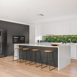 This is an example of a large contemporary l-shaped open plan kitchen in Sydney with a double-bowl sink, solid surface benchtops, window splashback, black appliances, light hardwood floors, with island, white benchtop, flat-panel cabinets, white cabinets and beige floor.