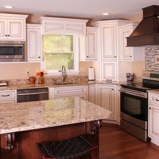 Große Klassische Wohnküche in L-Form mit weißen Schränken, Quarzwerkstein-Arbeitsplatte, Küchenrückwand in Braun, Küchengeräten aus Edelstahl, Kücheninsel, Unterbauwaschbecken, Kassettenfronten und braunem Holzboden in Philadelphia