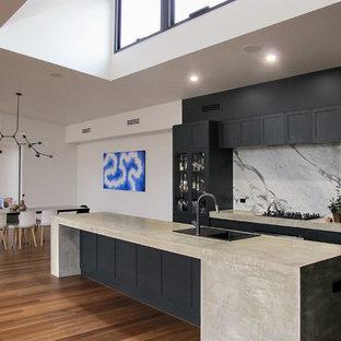 他の地域のモダンスタイルのおしゃれなキッチン (ダブルシンク、フラットパネル扉のキャビネット、黒いキャビネット、コンクリートカウンター、グレーのキッチンパネル、大理石のキッチンパネル、シルバーの調理設備、無垢フローリング、茶色い床、グレーのキッチンカウンター) の写真