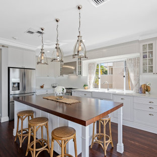 This is an example of a large transitional l-shaped eat-in kitchen in Gold Coast - Tweed with a farmhouse sink, shaker cabinets, white cabinets, wood benchtops, white splashback, porcelain splashback, stainless steel appliances, dark hardwood floors, with island, brown floor and brown benchtop.