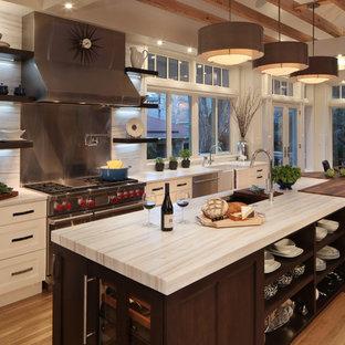 Große Klassische Wohnküche mit Unterbauwaschbecken, Schrankfronten mit vertiefter Füllung, weißen Schränken, Küchengeräten aus Edelstahl, braunem Holzboden, Kücheninsel und Rückwand aus Stein in Denver
