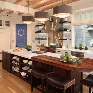Große Klassische Küche mit Landhausspüle, Schrankfronten mit vertiefter Füllung, weißen Schränken, Küchenrückwand in Metallic, Küchengeräten aus Edelstahl, braunem Holzboden, Kücheninsel und Rückwand aus Stein in Denver