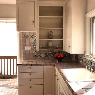 ロサンゼルスの小さいエクレクティックスタイルのおしゃれなキッチン (ドロップインシンク、シェーカースタイル扉のキャビネット、ベージュのキャビネット、タイルカウンター、ピンクのキッチンパネル、石タイルのキッチンパネル、白い調理設備、セラミックタイルの床、ピンクの床、ピンクのキッチンカウンター) の写真
